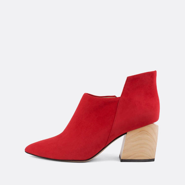 Pointed-toe red suede ankle boots with geometric cut and wooden block heel.