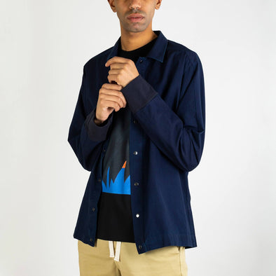 Navy blue denim overshirt with snap button closure.