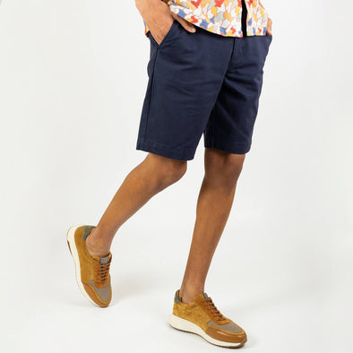 Navy blue casual shorts featuring two side pockets, a reverse button pocket, corozo (nut resin) buttons, and an internal drawstring.