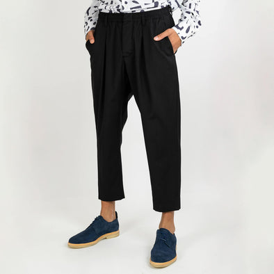 Black pleated trousers with cropped fit, button functioning fly and elasticated shirred waistband.