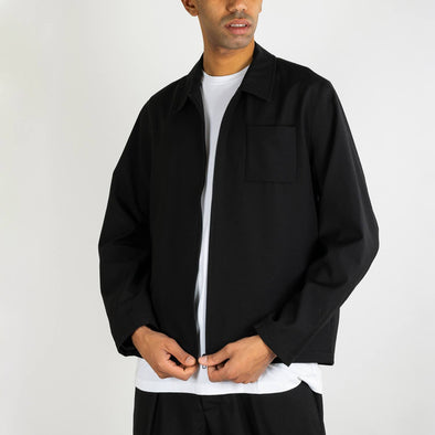 Straight boxy black jacket with concealed zip fastening, chest pocket and seamless side seam pockets.
