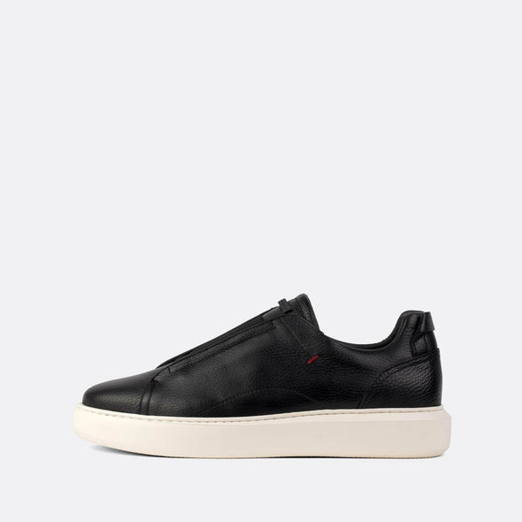 Black textured leather low-top sneakers with elasticated strap over the tongue.