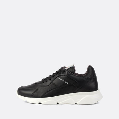 Black leather minimalist runners with a vibrant white sole.