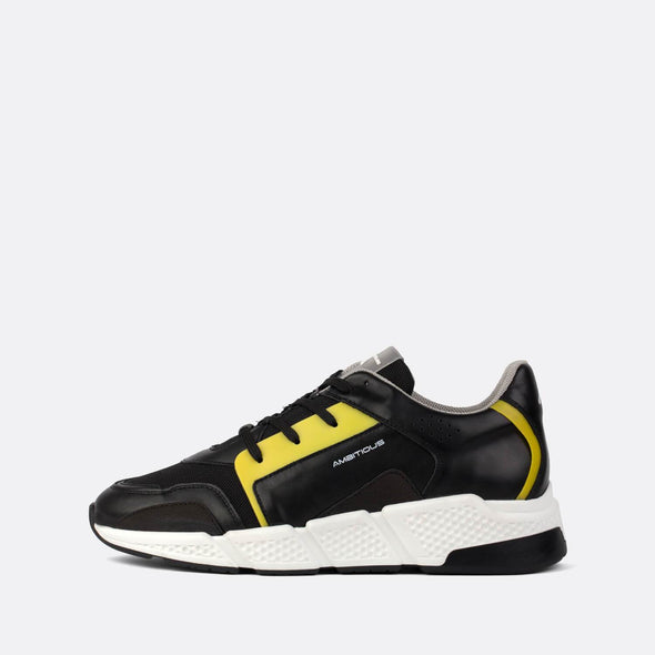 Black leather runners with a small mustard yellow details.