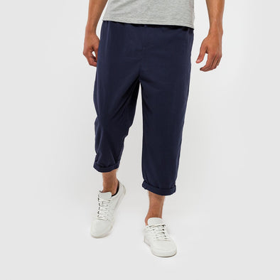 Navy blue loose fitted trousers with an elastic waist and back pocket.