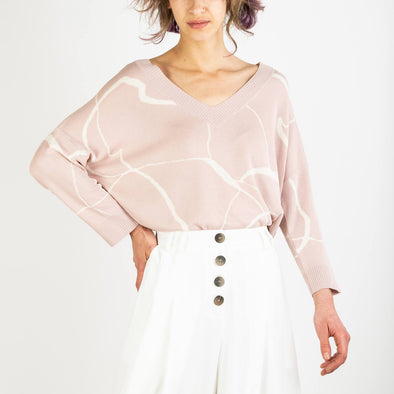 V-neck top with marble print and dip hem in blush and cream.