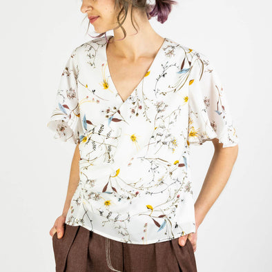 White v-neck top with floral print and ruffled sleeves.