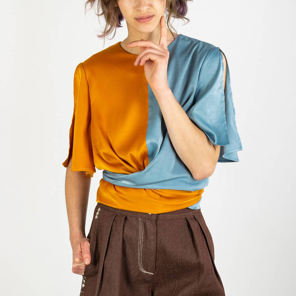 Two-tone satin wrap top with tie waist and split sleeves in metallic blue and rustic orange.