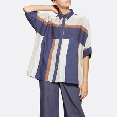 Boxy cut shirt featuring short sleeves and vibrant muiticolor stripes.
