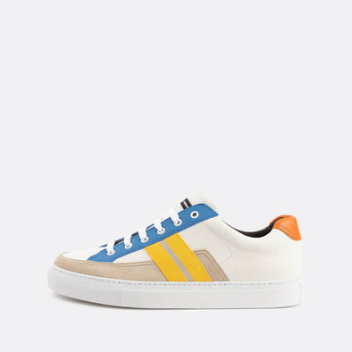 White low-top sneakers with pops of color in beige, yellow, orange and blue.