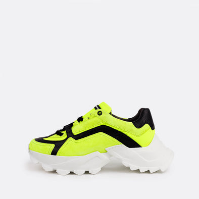 Edgy runners in black and neon yellow featuring an oversized white sole.
