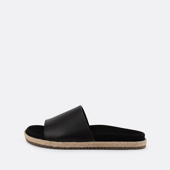 Black leather one-strap slides with raffia sole.