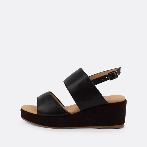 Black sandals with a black suede platform sole.