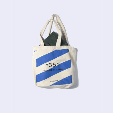 Beige totebag with blue diagonal large stripes and +351 logo print at the front.