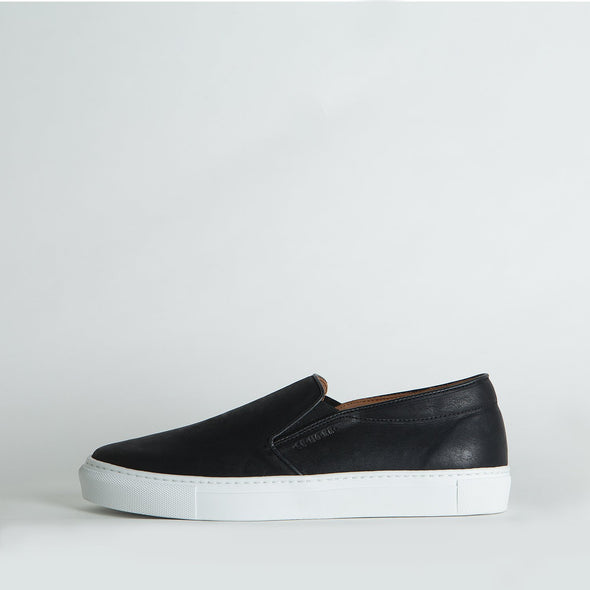Black leather slip-on sneakers with natural rubber soles.
