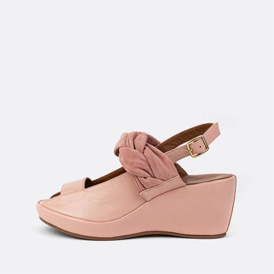 Pink leather ankle-tie platform sandals with side buckle fastening and braided detail.