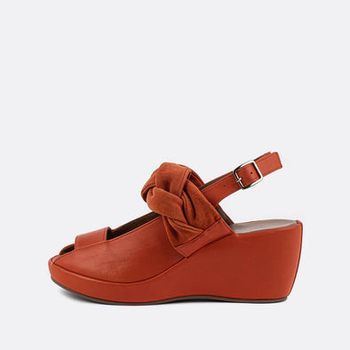 Orange red leather ankle-tie platform sandals with side buckle fastening and braided detail.