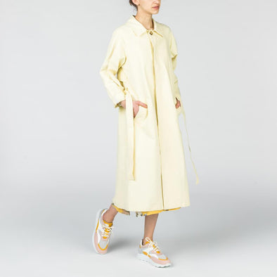 Soft yellow trench coat with a belt at the waist.