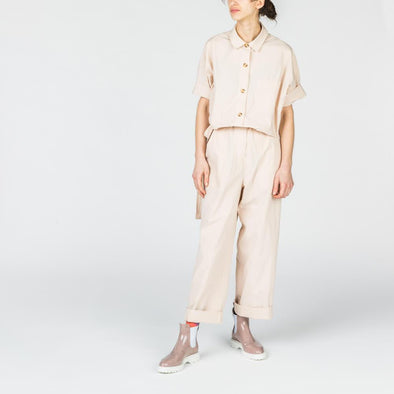 Beige jumpsuit with shirt collar and front and side pockets.