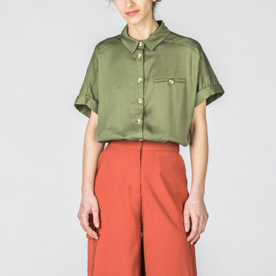Olive green shirt with short rolled up sleeves.