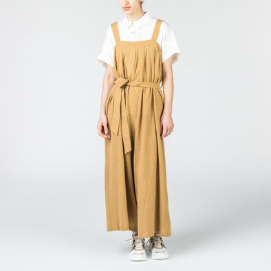 Beige wide leg jumpsuit with a belt to tie at the waist.