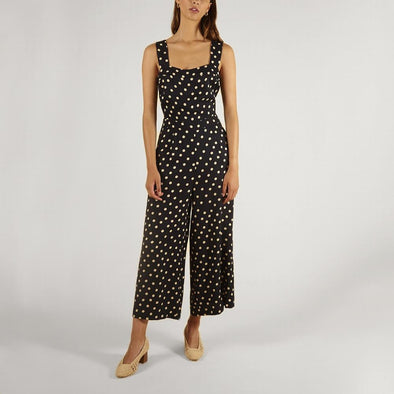 Black wide cut jumpsuit with white polka dot print and bow on the back.