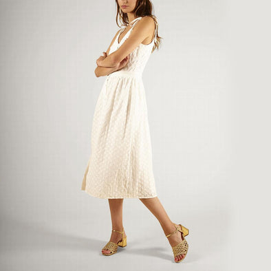 V-neck white dress with thin straps and floral embroidery.