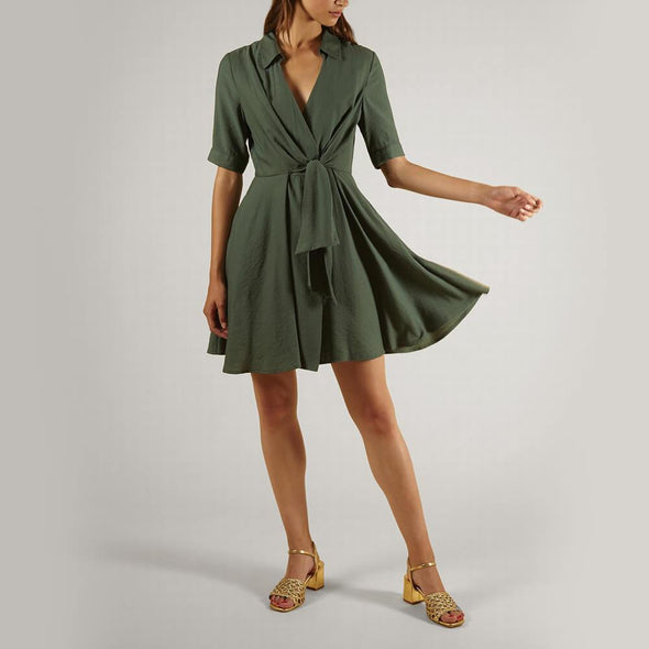 Short green dress with a bow at the front.