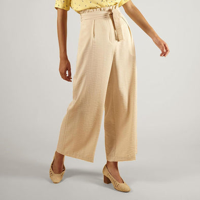 Beige wide cut trousers with side pockets and a belt.