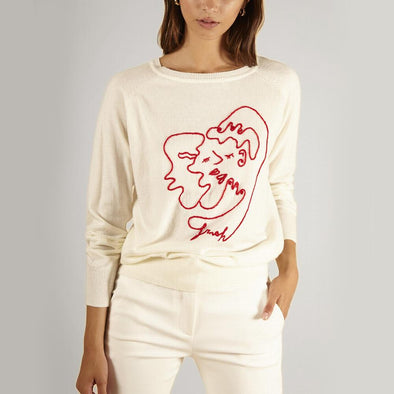 White sweater with red embroidery at the front.