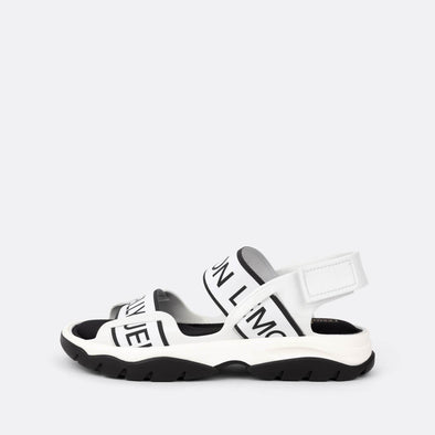White sandals with black logo details.