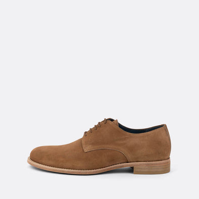 Brown derby shoes with lace-up closure and an almond-shaped toe.