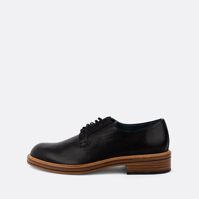 Black leather derby shoes with lace-up closure and an almond-shaped toe.