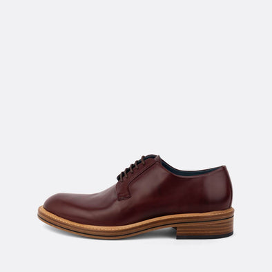 Bordeaux leather derby shoes with lace-up closure and an almond-shaped toe.