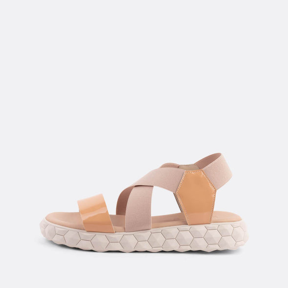 Flat cross-strap sandals in pale pink featuring a detailed chunky nude sole.