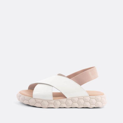 Flat cross-strap sandals in white and light pink featuring a detailed chunky nude sole.