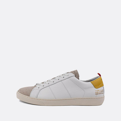 White sneakers with yellow detail on the heel.