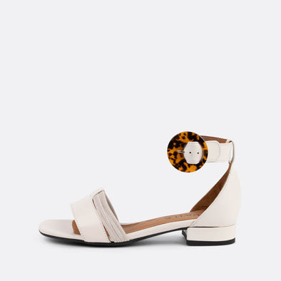 White suede flat sandals with distinct ankle buckle.