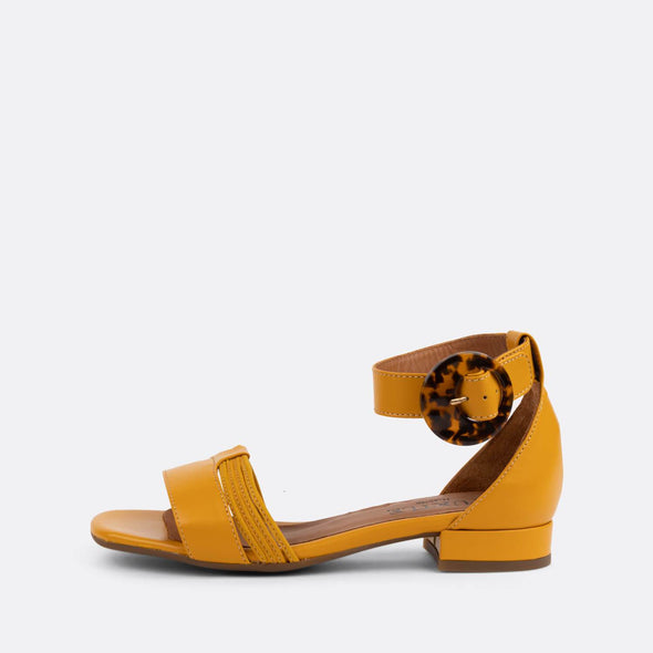 Yellow leather flat sandals with distinct ankle buckle.