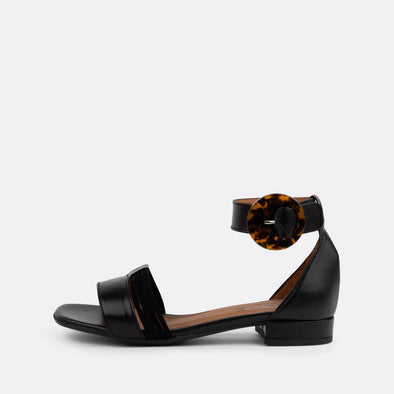 Black leather flat sandals with distinct ankle buckle.