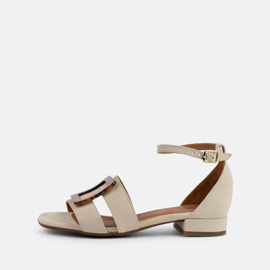 Beige suede flat sandals with thin straps connected by a buckle.