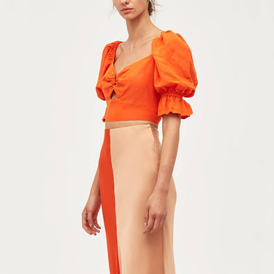Orange top with balloon sleeves and ring at the front.