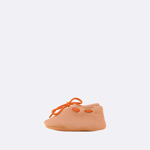 Soft baby slippers in cream leather with orange laces.