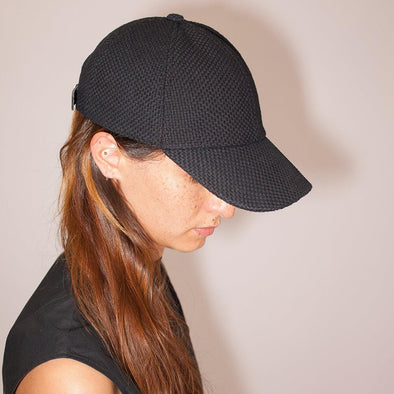 Black round cap with leather adjuster.