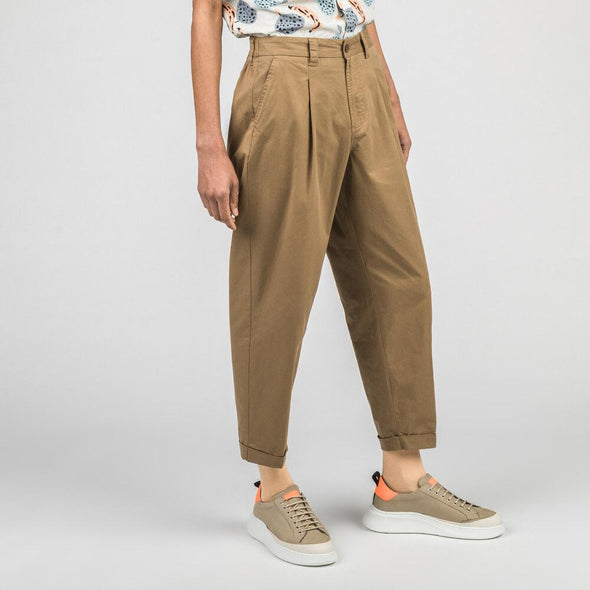 Beige standard fit pants with half elastic waist and pressed pleats.