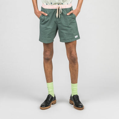 Green board shorts with elastic waistband, side mesh pockets and back patch pocket.