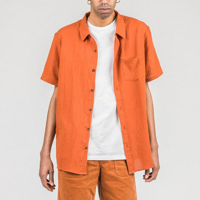 Orange short sleeved shirt with coconut buttons and chest pocket.
