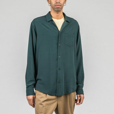 Olive green long sleeved shirt with coconut buttons and chest pocket.