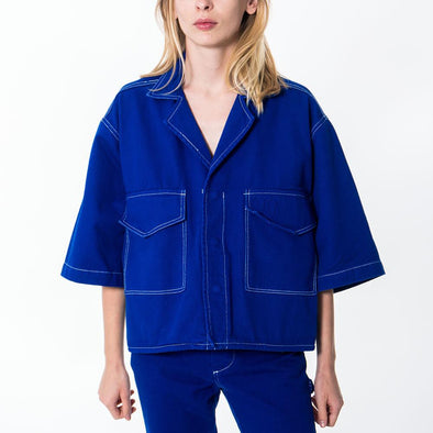 Straight line blue boxy shirt with big pockets and embroidered logo.