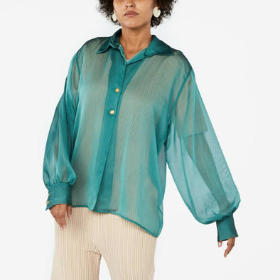Green see-through shirt with balloon sleeves and mustard yellow buttons.